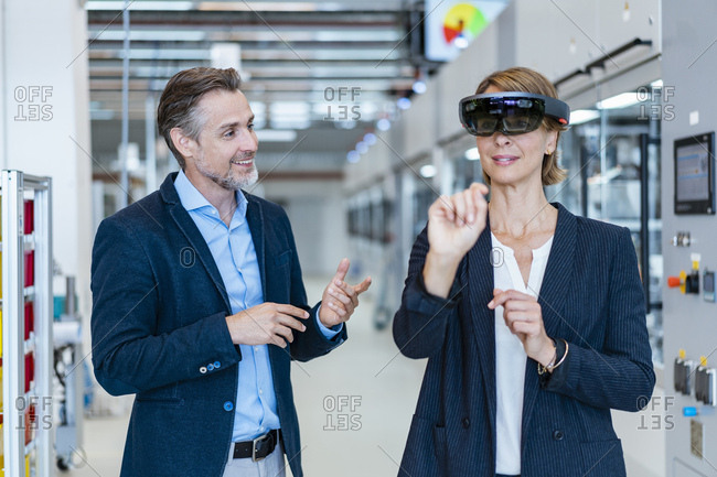 Businesswoman with AR glasses and businessman in a modern factory