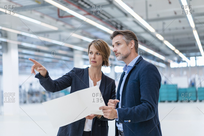 Businessman and businesswoman discussing plan in a factory hall