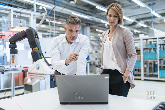 Businessman and businesswoman with laptop talking in a modern factory hall