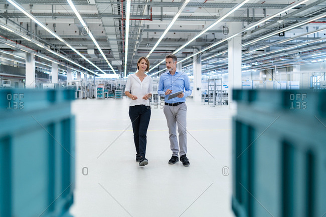 Businessman and businesswoman with tablet talking in a factory hall