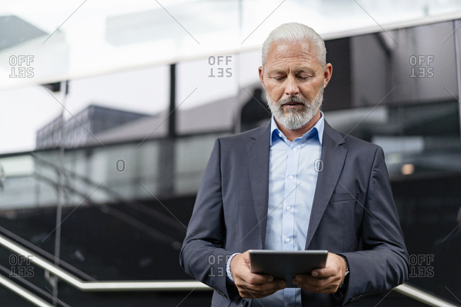Mature businessman on a journey using tablet
