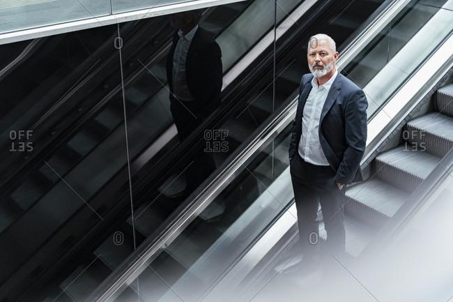 Mature businessman on an escalator
