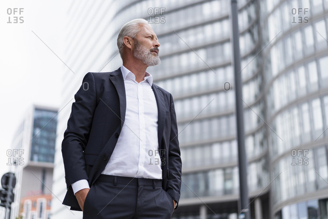 Mature businessman looking around in the city