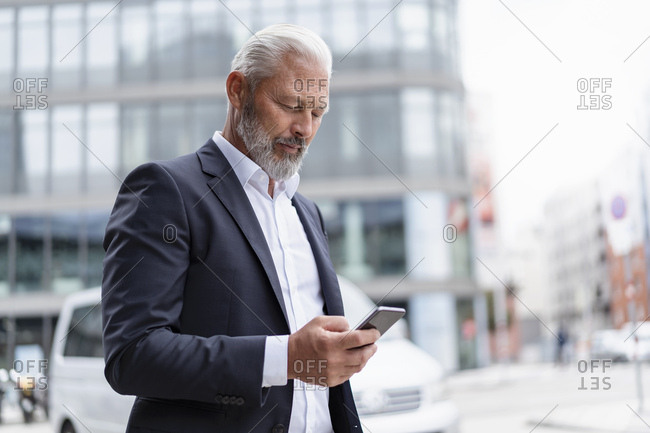 Mature businessman using cell phone in the city
