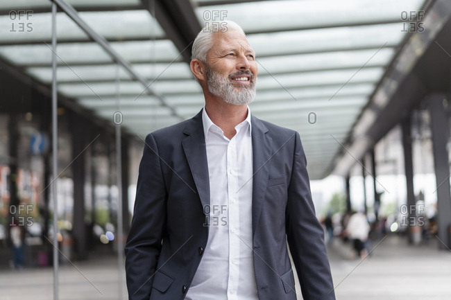 Smiling mature businessman in the city on the go