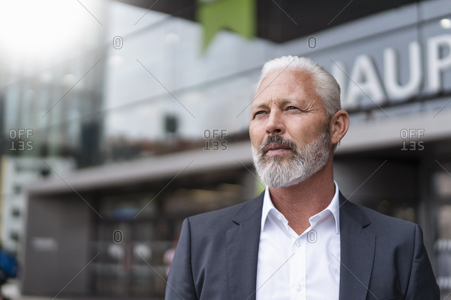 Mature businessman looking around at the train station