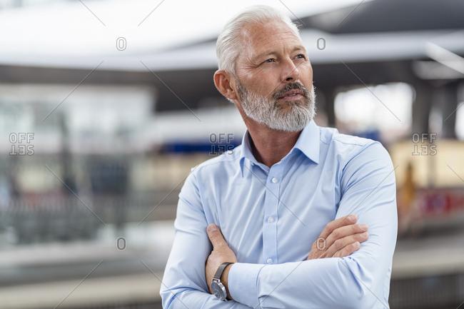 Mature businessman at the station platform looking around