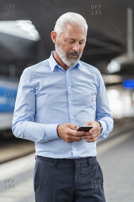 Mature businessman using cell phone at the station platform