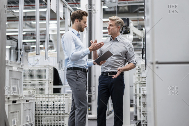 Two businessmen with tablet talking in a modern factory