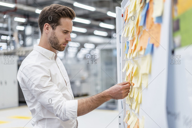 Businessman organizing adhesive notes on a board in a factory