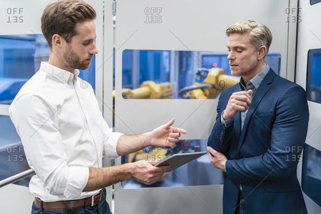 Two businessmen talking at robot in a modern factory