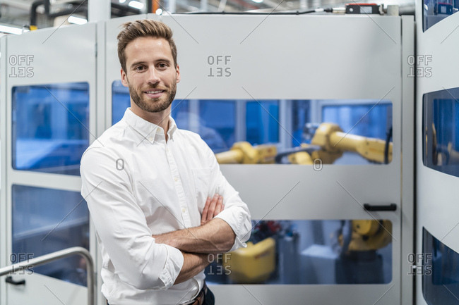 Portrait of a smiling businessman in front of a robot in a modern factory