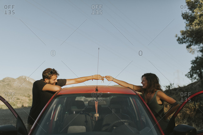 Couple exchanging car keys on a road trip