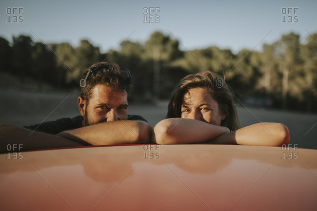 Happy couple on a road trip- taking a break- leaning on car roof