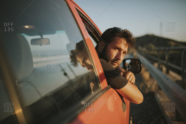 Man on a road trip looking out of car window