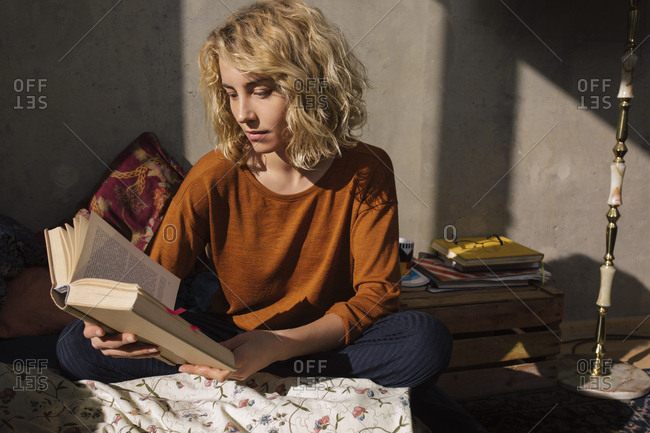 Blond student sitting on bed reading a book