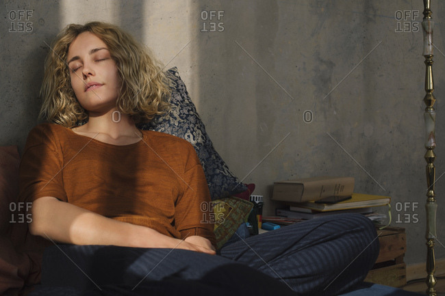 Portrait of student sitting on bed relaxing