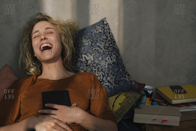 Portrait of laughing young woman lying on bed with E-book reader