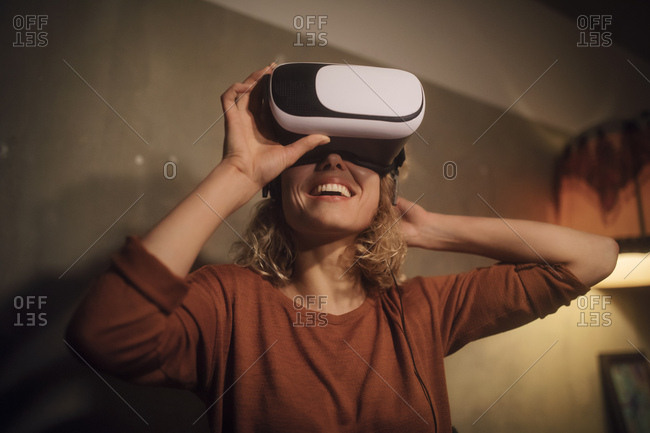 Laughing young woman putting on Virtual Reality Glasses at home