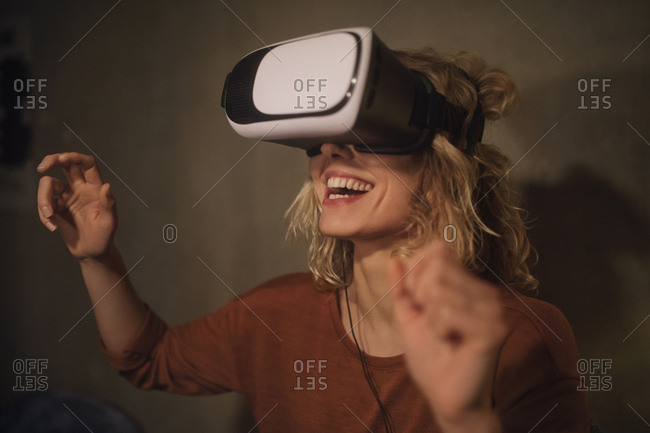 Laughing young woman using Virtual Reality Glasses at home