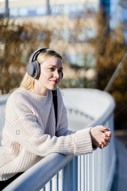 Portrait of content young woman leaning on railing of footbridge listening music with headphones