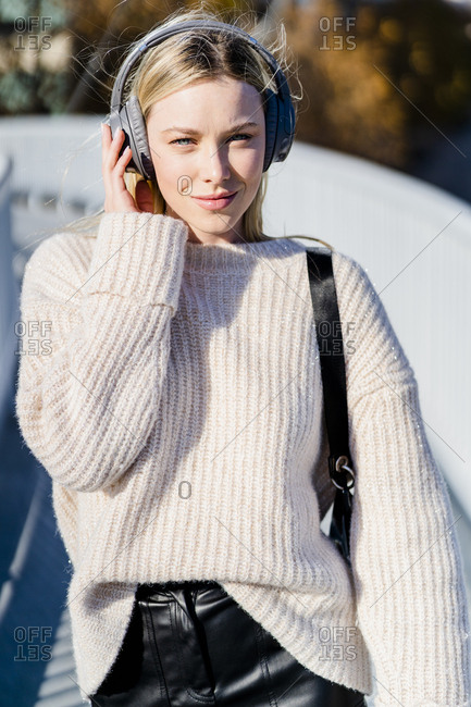 Portrait of content young woman listening music with headphones outdoors