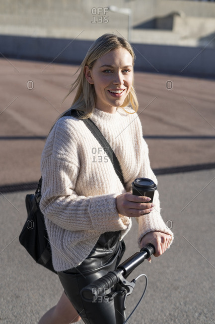 Portrait of smiling young woman with sports bag- kick scooter and coffee to go
