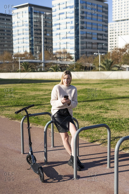 Young woman with kick scooter using smartphone