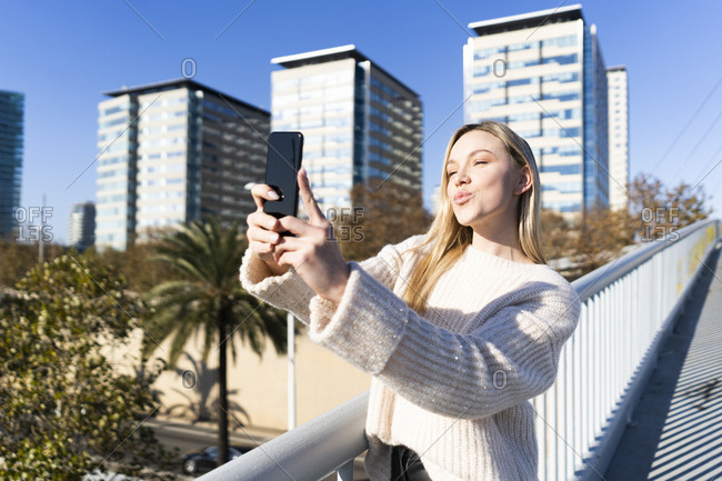 Portrait of blond young woman on footbridge talking selfie with smartphone