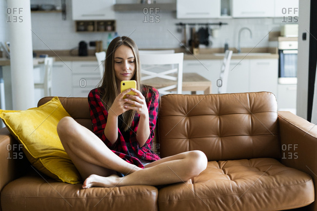 Young woman using cell phone on a couch at home