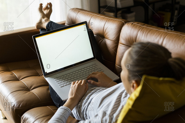 Young woman lying on couch at home using laptop