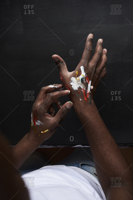 Dirty hands of artist with colorful paints against black background. London- UK.