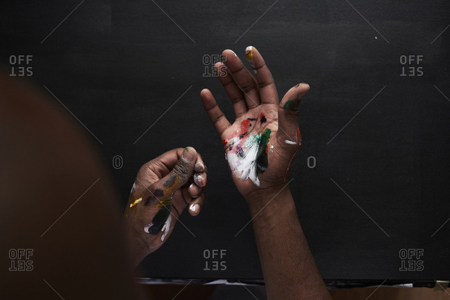 Dirty hands of artist with colorful paints against black background