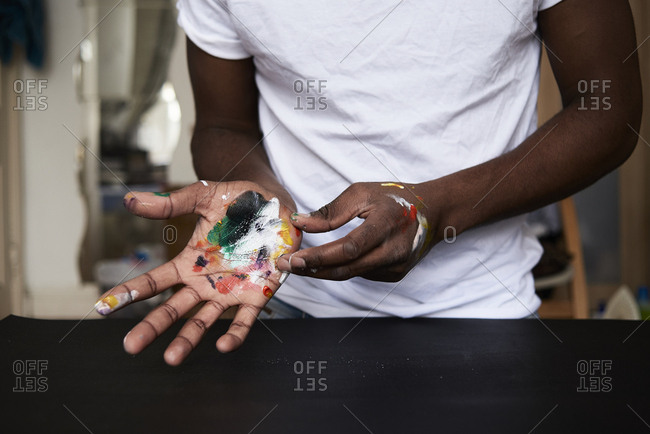 Dirty hands of artist with colorful paints- close up