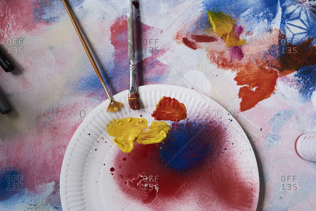 Paper plate with acrylic paints on canvas painting in artist studio