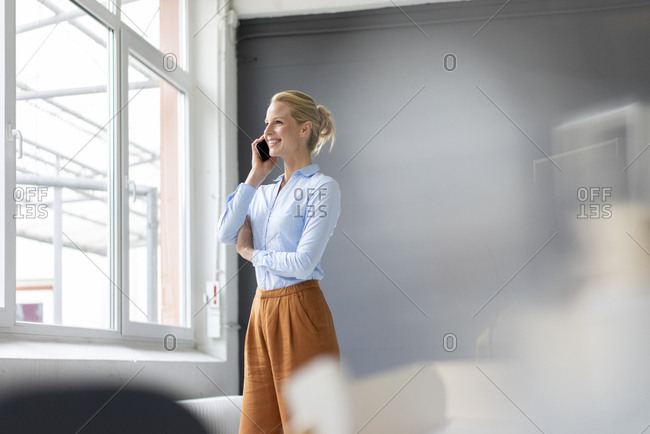 Smiling young businesswoman talking on cell phone in office