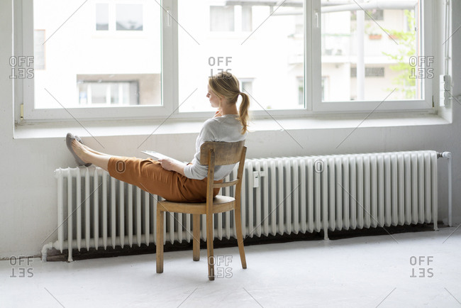 Young woman sitting on chair at the window in office