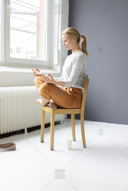 Young woman sitting on chair in office practicing yoga