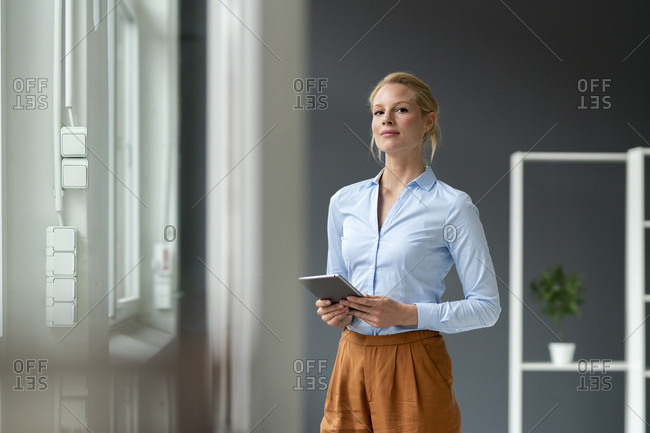 Portrait of young businesswoman with tablet in office