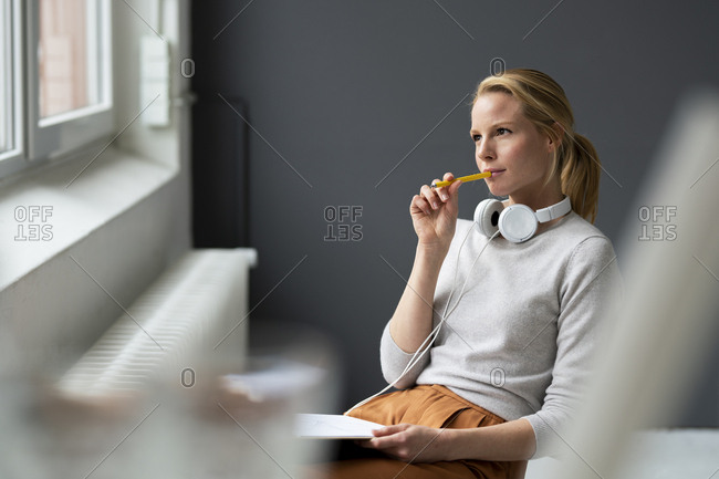 Young woman sitting on chair at the window in office thinking