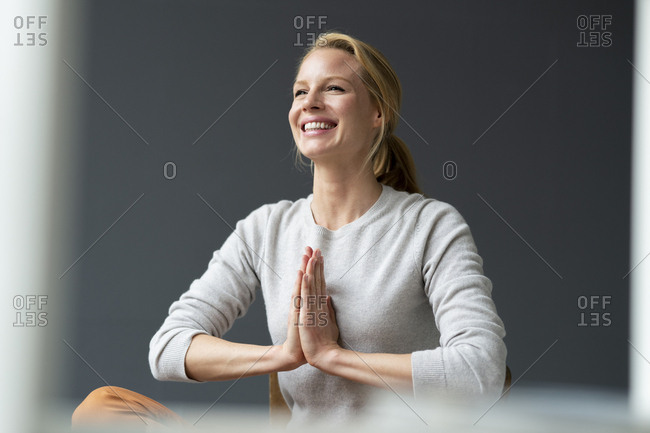 Happy young woman with clasped hands
