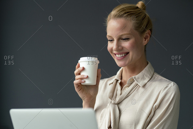 Smiling young businesswoman with laptop and takeaway coffee