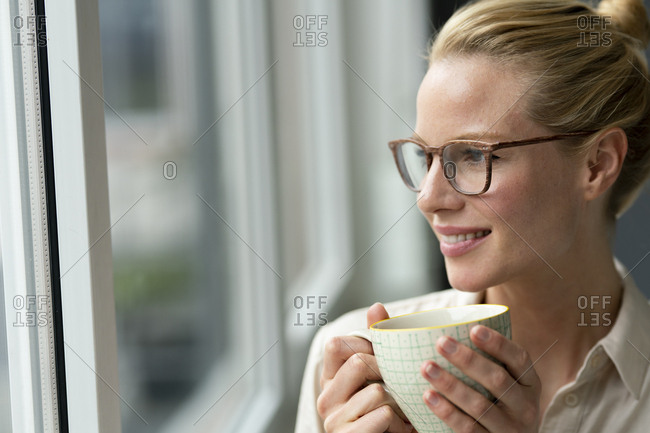 Young businesswoman with cup of coffee looking out of window
