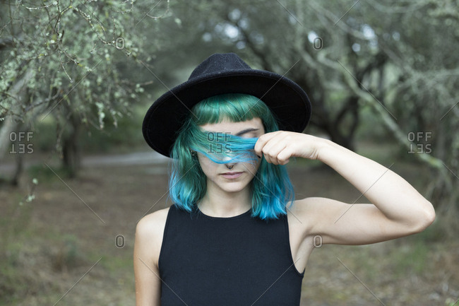Portrait of young woman with dyed blue and green hair wearing black hat on rainy day
