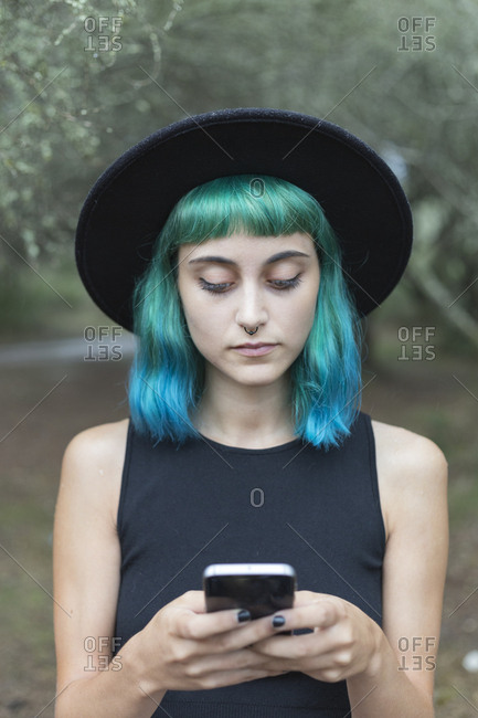 Portrait of young woman with dyed blue and green hair and nose piercing using smartphone