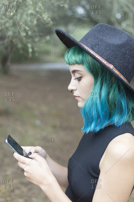 Profile of young woman with dyed blue and green hair using smartphone on rainy day