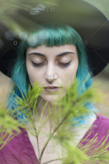 Portrait of young woman with dyed blue and green hair and nose piercing in nature