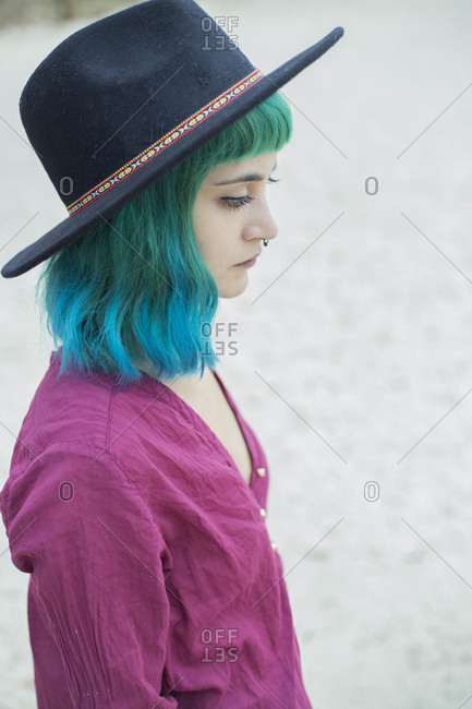 Portrait of young woman with dyed blue and green hair and nose piercing outdoors
