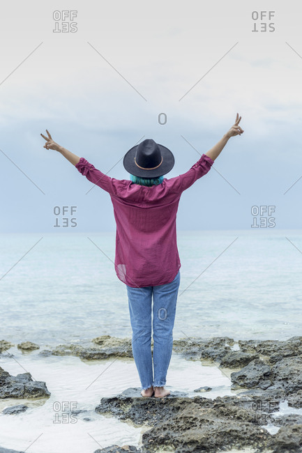 Back view of young woman with dyed blue hair standing on rock in front of the sea showing victory signs- Spain