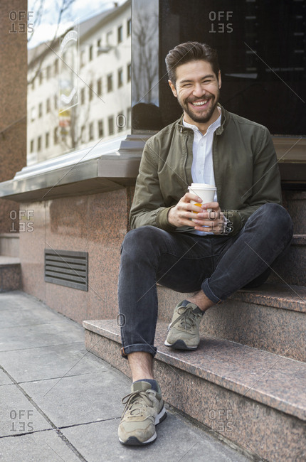 Portrait of laughing young man sitting on steps with coffee to go